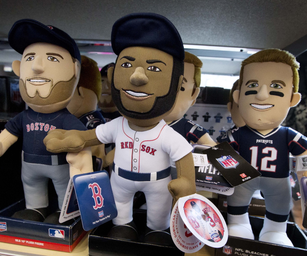 Dolls depict New England Patriots quarterback Tom Brady, right, and Boston Red Sox players David Ortiz, center, and Dustin Pedroia at the CityTarget store in Boston.