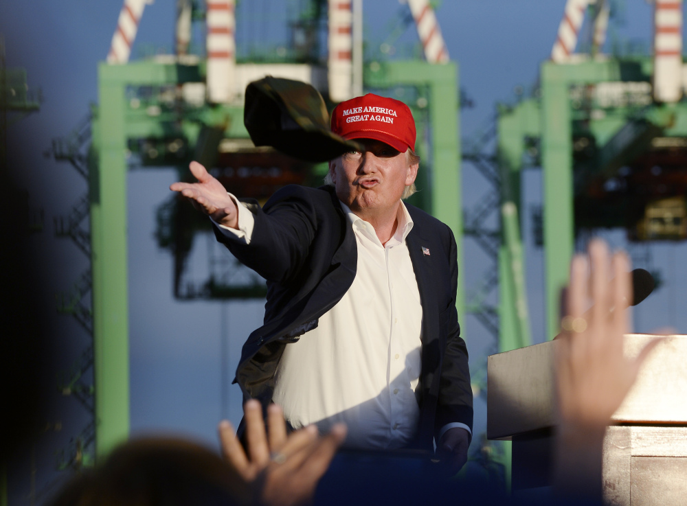 Republican presidential candidate Donald Trump throws a baseball cap from the stage after speaking to supporters at campaign event aboard the USS Iowa battleship in Los Angeles Tuesday.