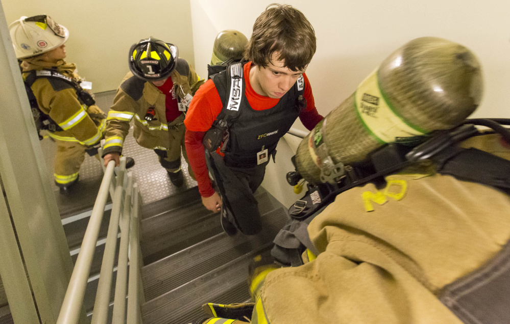 Firefighter Mike Gallagher, center, of the Ellington, Conn., fire department was one of about 100 participants to climb the stairs at 2 Monument Square on Sunday in remembrance of the firefighters lost on Sept. 11 and to raise money for the National Fallen Firefighters Foundation.