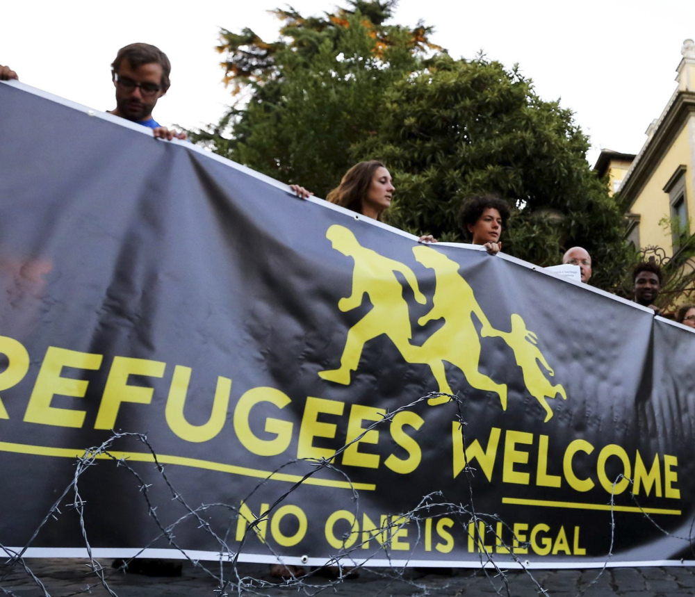 Activists hold a banner in front of the Hungarian Embassy in Rome. Hungary, Romania, the Czech Republic and Slovakia voted against spreading asylum-seekers across Europe.
