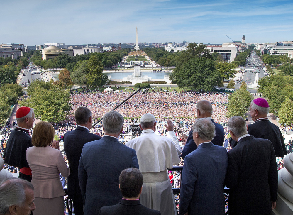 Pope Francis waves to the assembled crowd from the Speakers Balcony at the U.S. Capitol with members of Congress on Thursday. Doug Mills/The New York Times via AP