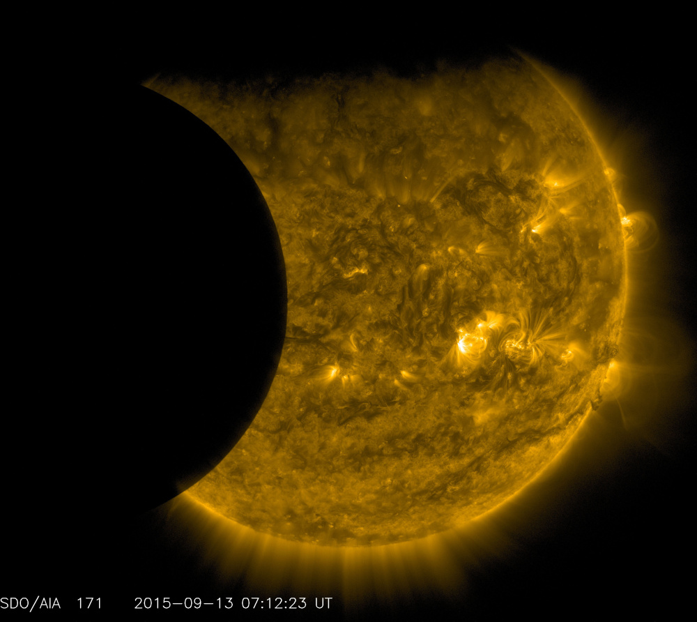 The moon, left, and the Earth, top, transit the sun together on Sept. 13, as seen from the Solar Dynamics Observatory. The edge of Earth appears fuzzy because the atmosphere blocks different amounts of light at different altitudes. This image has been colorized in gold.