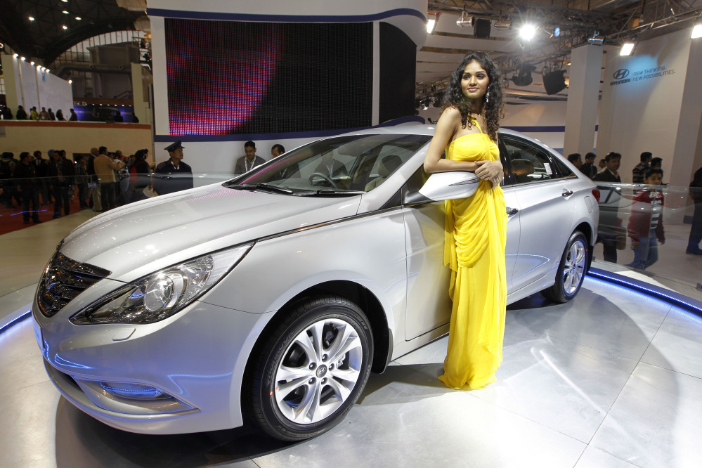 In this Jan. 6, 2012 file photo, a model poses near the new version of Hyundai Sonata displayed at the Hyundai stall during Auto Expo in New Delhi, India. Hyundai is recalling nearly a half-million midsize cars in the U.S. to replace key engine parts because a manufacturing problem could cause them to fail.