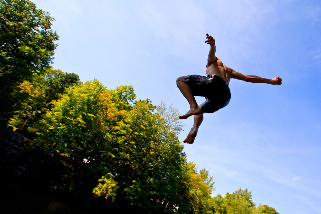 John Vedral, 17, of Buxton, jumps off a rock face into the Saco River in Buxton on Wednesday. He and a group of fellow Bonny Eagle High School students went swimming to cool off after they were dismissed early because of dangerously warm classrooms as  outside temperatures climbed into the 90s.