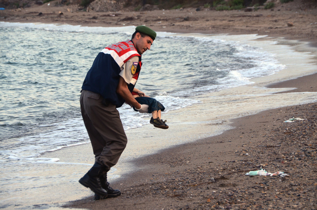 A paramilitary police officer carries the lifeless body of Aylan Kurdi, 3, after a number of migrants died and a smaller number were reported missing after boats carrying them to the Greek island of Kos capsized, near the Turkish resort of Bodrum early Sept. 2. The Associated Press