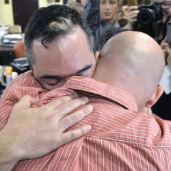 James Yates, left, hugs his partner William Smith Jr., after receiving their marriage license at the Rowan County Judicial Center in Morehead, Ky., Friday.  Deputy Clerk Brian Mason issued the license, congratulating the couple and shaking their hands as he smiled. The Associated Press
