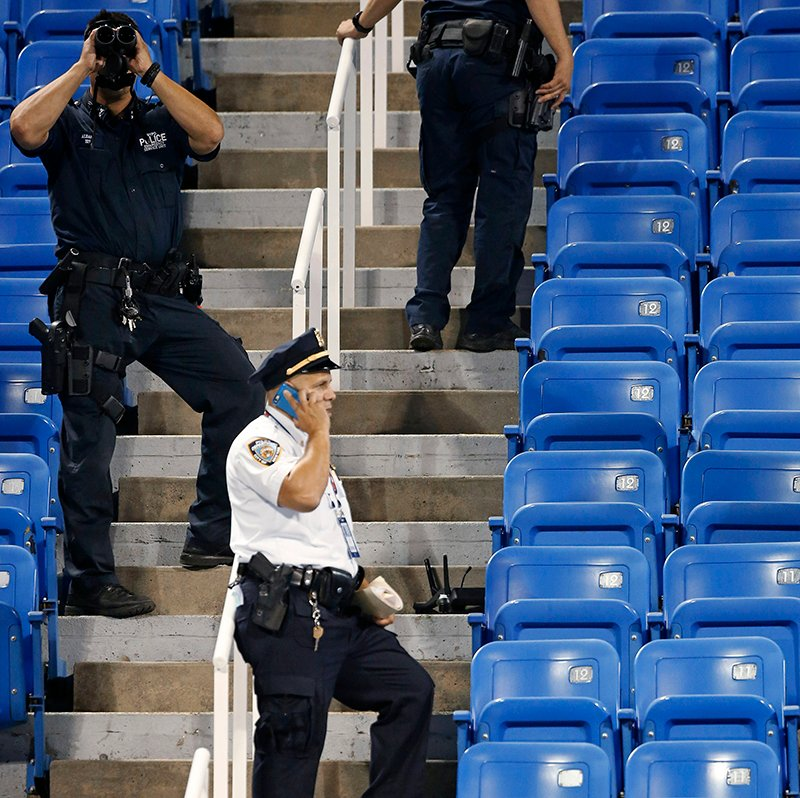 Police officers investigate an unoccupied corner of Louis Armstrong Stadium after a drone flew over the court, buzzing the players during a match between Flavia Pennetta, of Italy, and Monica Niculescu, of Romania. The drone crash-landed in the seats and can be seen to the right of the police officer on his phone.