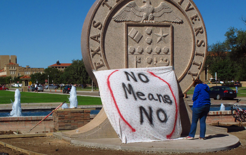 """A Texas Tech student helps drape a bed sheet with the message """"No Means No"""" over the university's seal at the Lubbock campus to protest what students say is a """"rape culture"""" on campus. In a survey of two dozen American universities, one-quarter of the undergraduate women said they had experienced unwanted sexual contact while at college."""