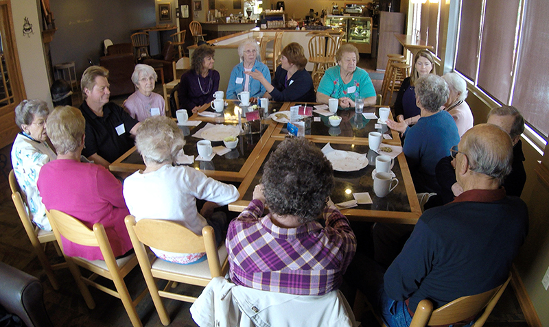 "A group of people with dementia, their caregivers and officials from a local nursing home talk, drink coffee and eat cookies at Connections Cafe in Watertown, Wis., in May. The support and social group called ""Memory Cafe"" is part of the city's efforts to become a dementia friendly city. The Associated Press"