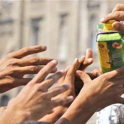 Migrants receive a juice donation in front of the railway station in Budapest Thursday. Over 150,000 migrants have reached Hungary this year, most coming through the southern border with Serbia. Many apply for asylum but quickly try to leave for richer EU countries. The Associated Press