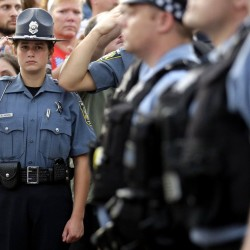 A police Explorer salutes as police officials follow Fox Lake Police Lt. Charles Joseph Gliniewicz's family after a vigil Wednesday in Fox Lake, Ill. The Associated Press