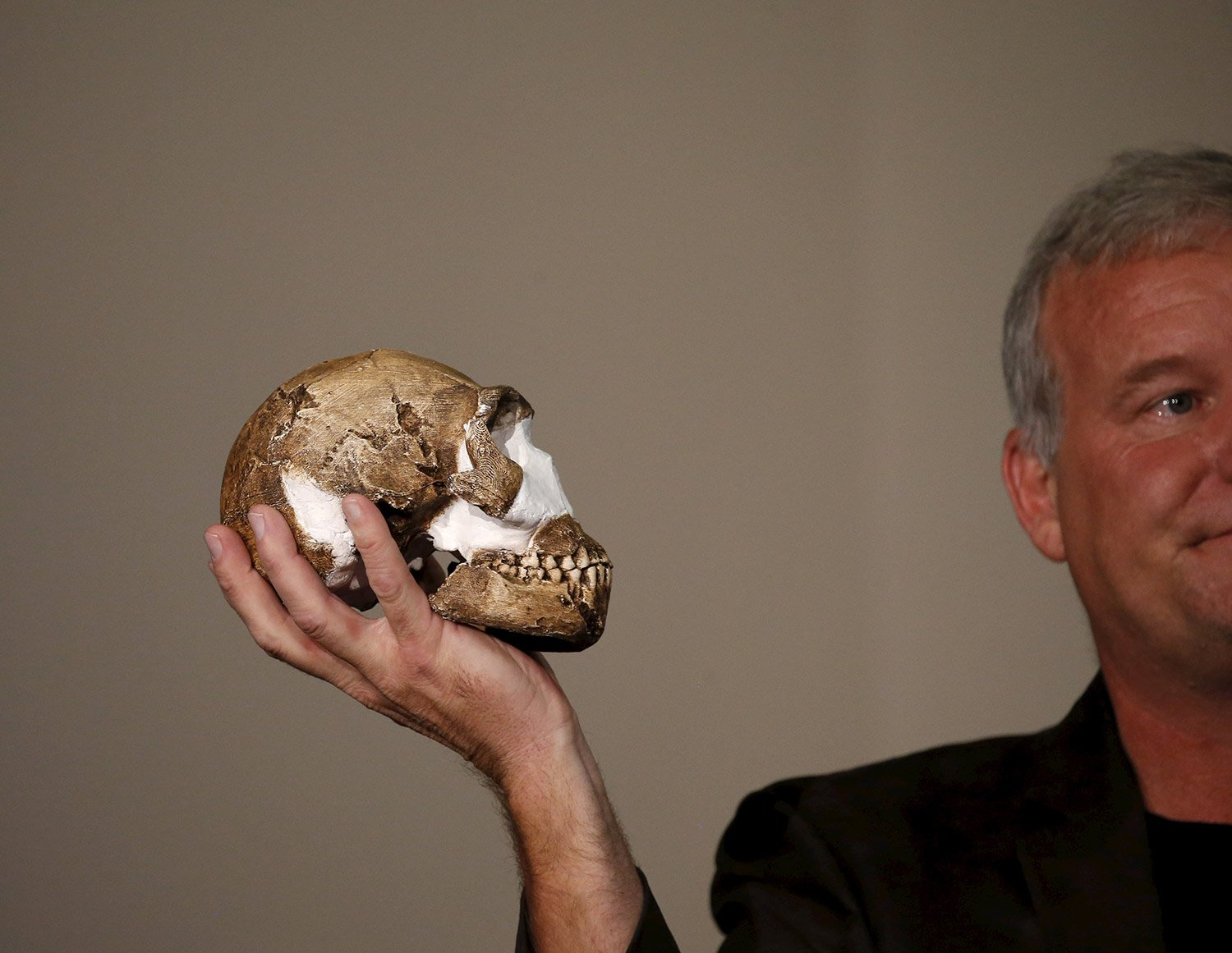 "Professor Lee Berger holds a replica of the skull of a newly discovered ancient species, named ""Homo naledi"", during its unveiling outside Johannesburg. Reuters"