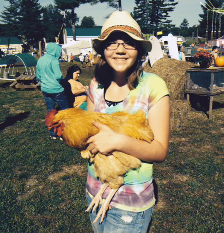 Lia Herrick, 13, of Harmony, holds Reggie, her 3-month-old rooster, which she showed in the poultry show Saturday at the Harmony Free Fair in Harmony.