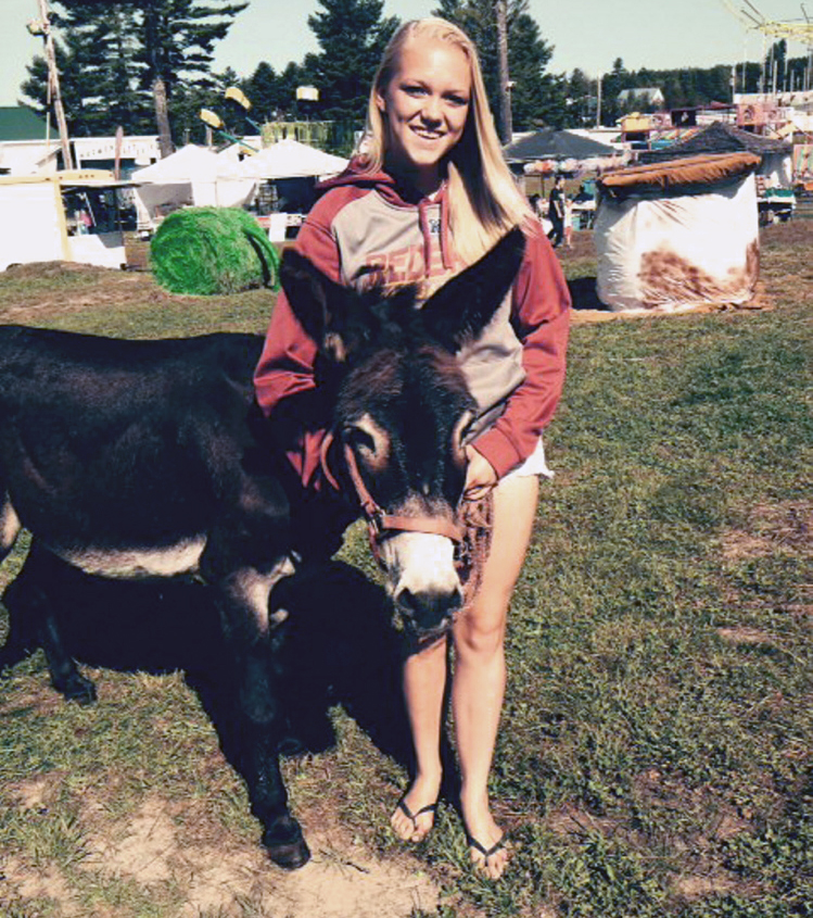 Marissa Muncey, 15, of Lincoln, stands with her donkey, Max, on Saturday at the Harmony Free Fair in Harmony. They won second place in the livestock contest.