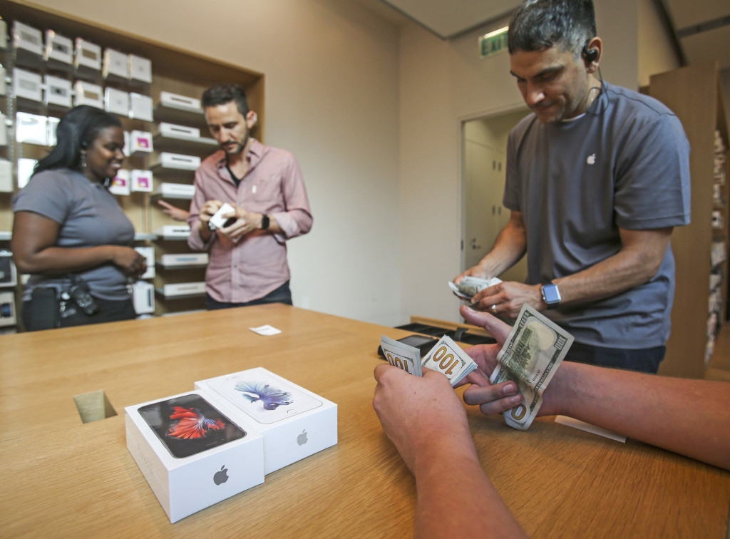 A customer pays with cash for his Apple iPhone 6s and iPhone 6s Plus smartphones at an Apple store in Los Angeles. The Associated Press