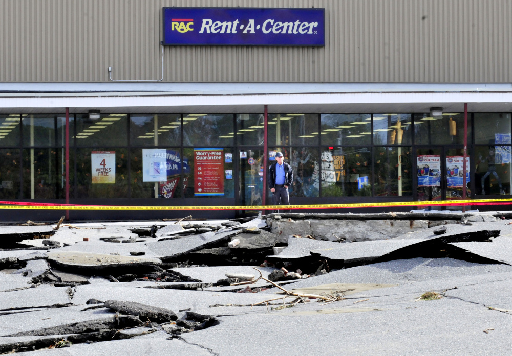 """Rent -A- Center employee Merle Gordon looks over the large sections of buckled pavement in the parking lot at a mini-mall in Skowhegan on Thursday. During the storm on Wednesday the truck Gordon usually drives sank in a hole as the water flooded the lot. """"I'm lucky it was my day off yesterday,"""" Gordon said."""