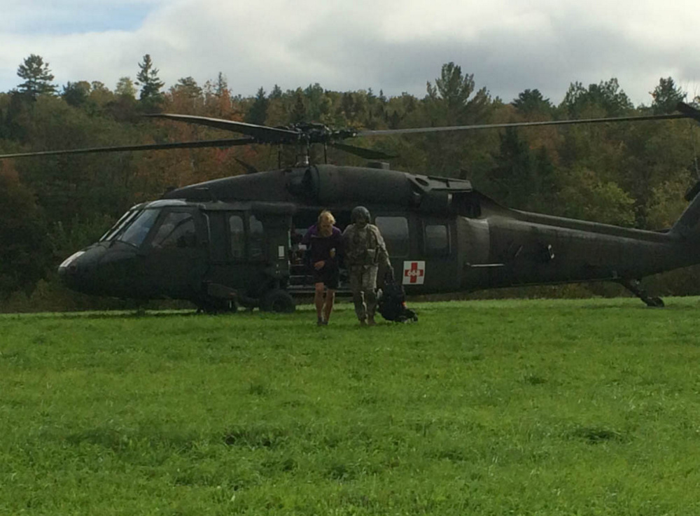 Appalachian Trail thru-hiker Gabrielle Grace is assisted away from a Maine Army National Guard Blackhawk helicopter by a crew member. Grace, 26, of Baltimore, Maryland, and two other women were cut off by the flooding East Branch of the Piscataquis River Thursday.