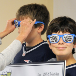 Katie Hoffman of the Maine Dairy and Nutrition Council places sunglasses on Pittston Consolidated School students Casey Paul, left, and Tommy Murphy on Thursday when the school received a check for $1,400 from the state council.