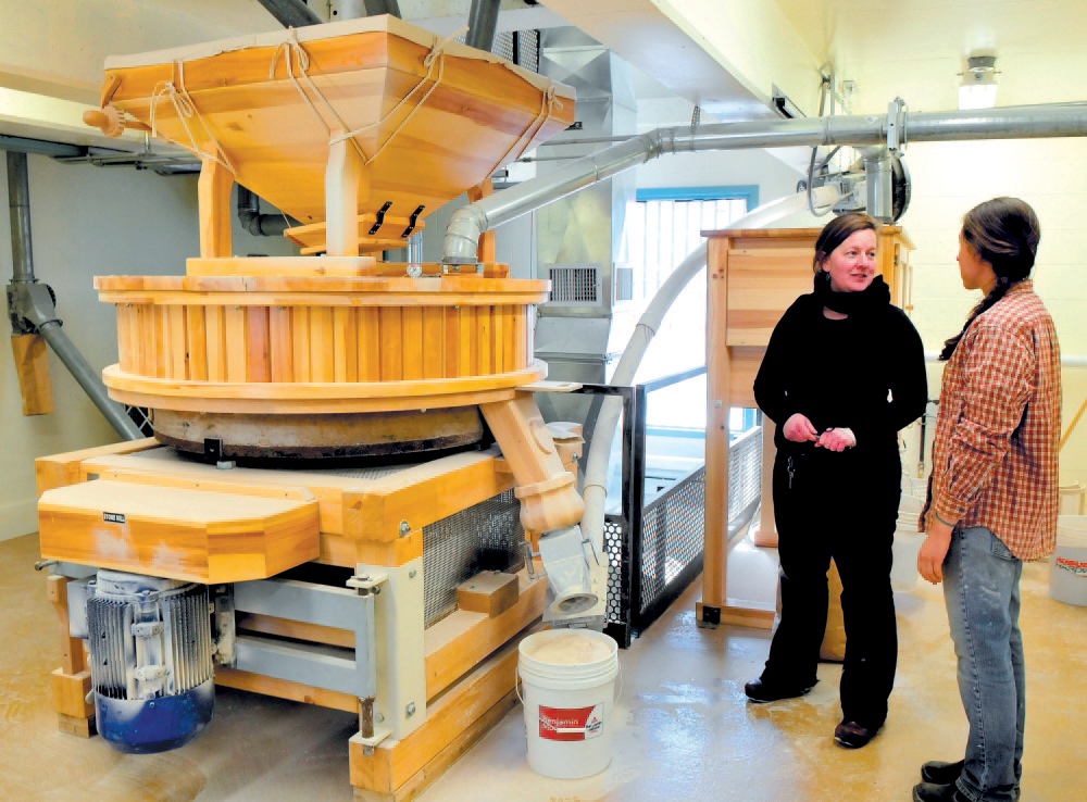 Amber Lambke, left, owner of Maine Grains, and head miller Julie Zavage discuss an order of flour being ground in the stone mill, left, at the Somerset Grist Mill in Skowhegan in 2013. A USDA grant will help help the mill buy new equipment.