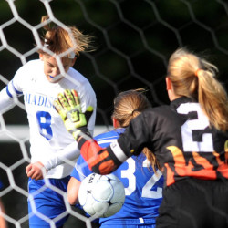 Madison High School's Kayla Bess (8) looks for the header on the corner kick as she is defended by Boothbay's Lisa Pawlowski (32) and goalie Jackie Mcloon (2) in the first half in Madison on Thursday, Oct. 1, 2015.