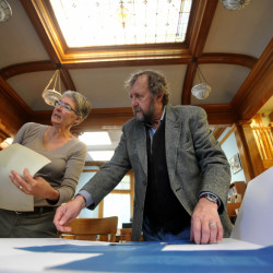 Lynne Hunter, left, adult services librarian, and David Olson, director of the Wilton Library, create a poster displaying architectural renderings of furniture in the Wilton Library on Goodspeed Street in Wilton on Friday. The library is celebrating it's 100th year Saturday.