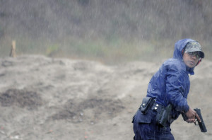 State Police Cadet Toral Nelson looks over her shoulder after firing at a target in the pouring rain in Augusta on Wednesday. Students enrolled in the Maine Criminal Justice Academy's Basic Law Enforcement Training Program practiced shooting from a variety of positions as part of the training program for new police officers.