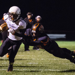 Portland Press Herald photo by Whitney Hayward   Skowhegan wide receiver Jon Bell escapes the tackle of Brunswick's Ben Palizay en route to the end zone Friday night in Brunswick.