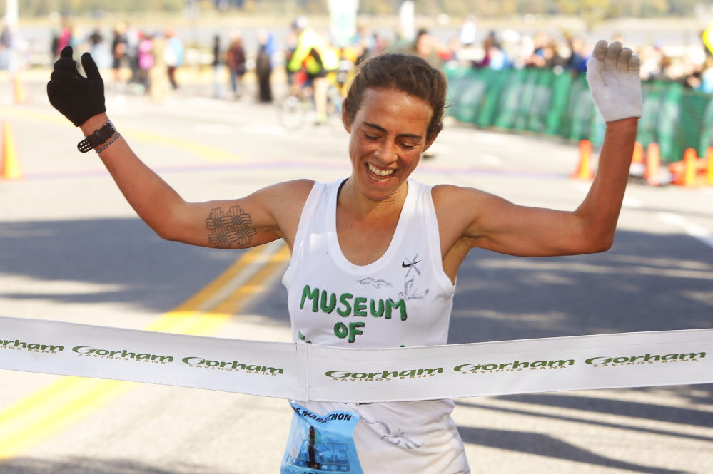 Leah Frost, 32 of Glover, Vermont, jubilantly crosses the finish line to win the women's division in Sunday's Maine Marathon in Portland.