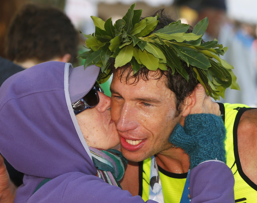Maine Marathon men's winner Evan Graves, 34, receives a congratulatory kiss from his mother, Roxie Brechlin, of Bar Harbor at the finish line Sunday in Portland.