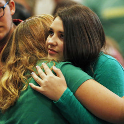Lacey Scroggins, right, receives a hug during a church service at the New Beginnings Church of God Sunday, Oct. 4, 2015, in Roseburg, Ore. Scroggins is a survivor of the fatal shooting at Umpqua Community College. (AP Photo/John Locher)