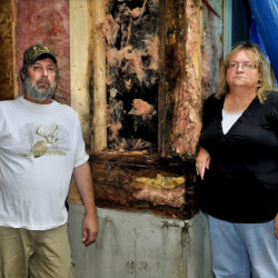 Chris and Janet Weeks stand beside a rotting section of the front of their home Tuesday in Oakland. The Weekses claim the builder of the 14-year-old home failed to prevent rainwater from infiltrating the building wall and causing the sheathing and framing materials to rot.