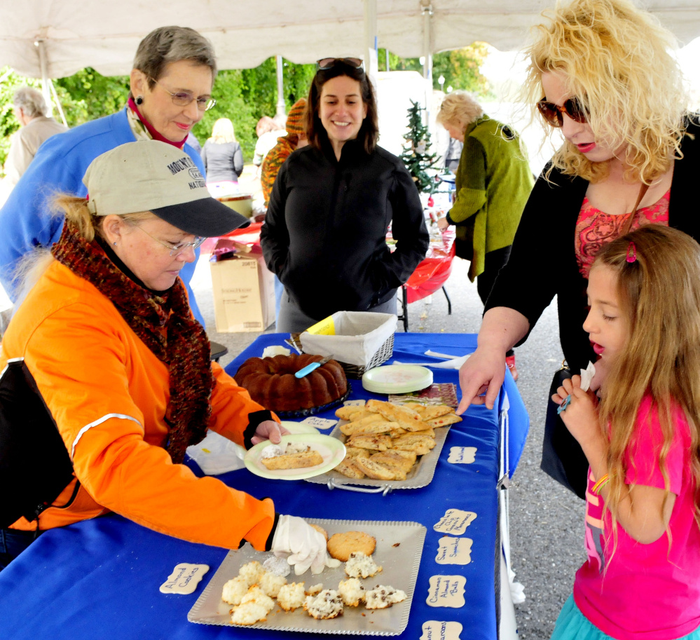 Amelia Berls and her mother, Amy, select desserts from the Beth Israel Synagogue booth on Sunday during the Harvest Fest and Festival at the Falls event in Waterville. Serving is Judy Hansen, left, as  Barbara Jolovitz-Childers and Rabbi Rachel Isaacs watch.