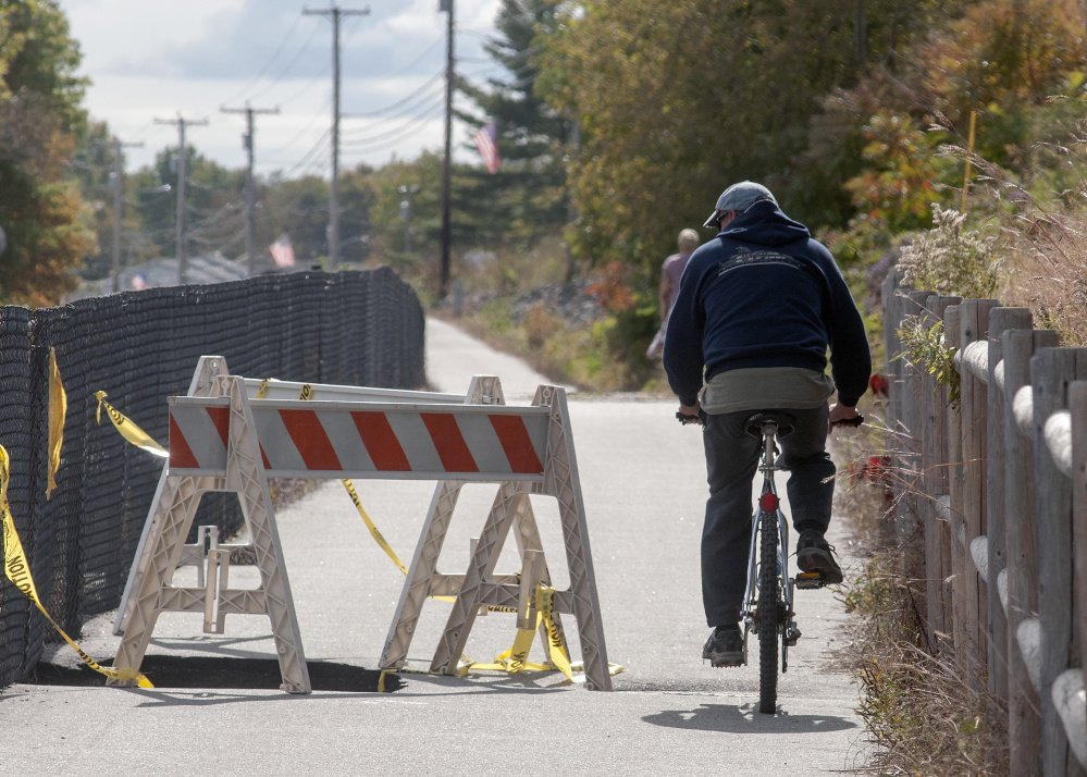 Marc Poirier looks down into the collapsed pavement as he rides past one of two washed out sections of the Kennebec River Rail Trail on Monday in Farmingdale.