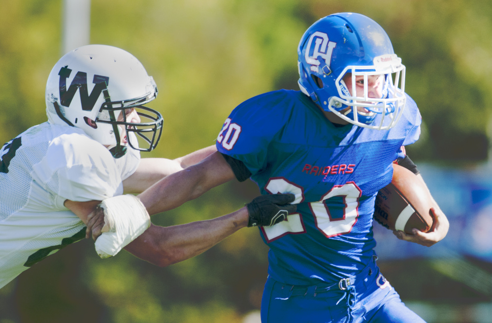 Staff photo by Joe Phelan   Winthrop/Monmouth's Ben Ames, left, tries to tackle Oak Hill running back Levi Buteau during a game Saturday in Wales.