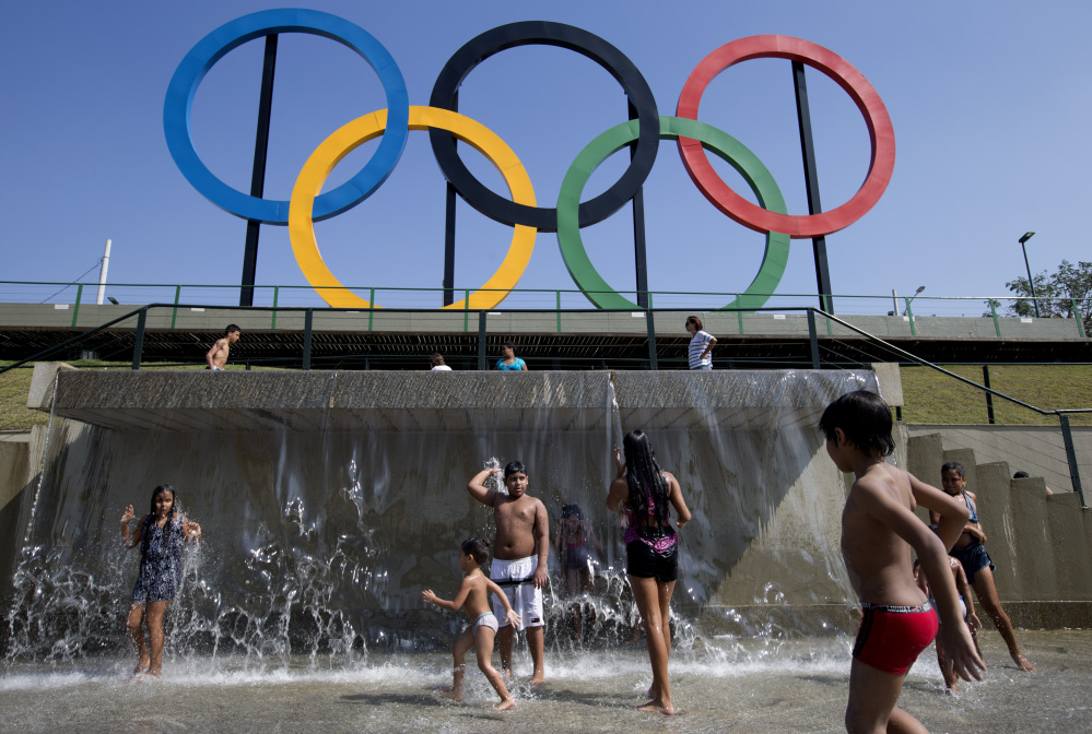 FILE - In this July 28, 2015 file photo, children play in a water fountain next to Olympic rings at Madureira Park in Rio de Janeiro, Brazil.
