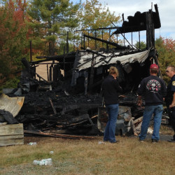 Homeowner Larry Hewins, center, looks at the wreckage of his burned out house Wednesday morning with Leeds Fire Chief Glenn Holt, at right.