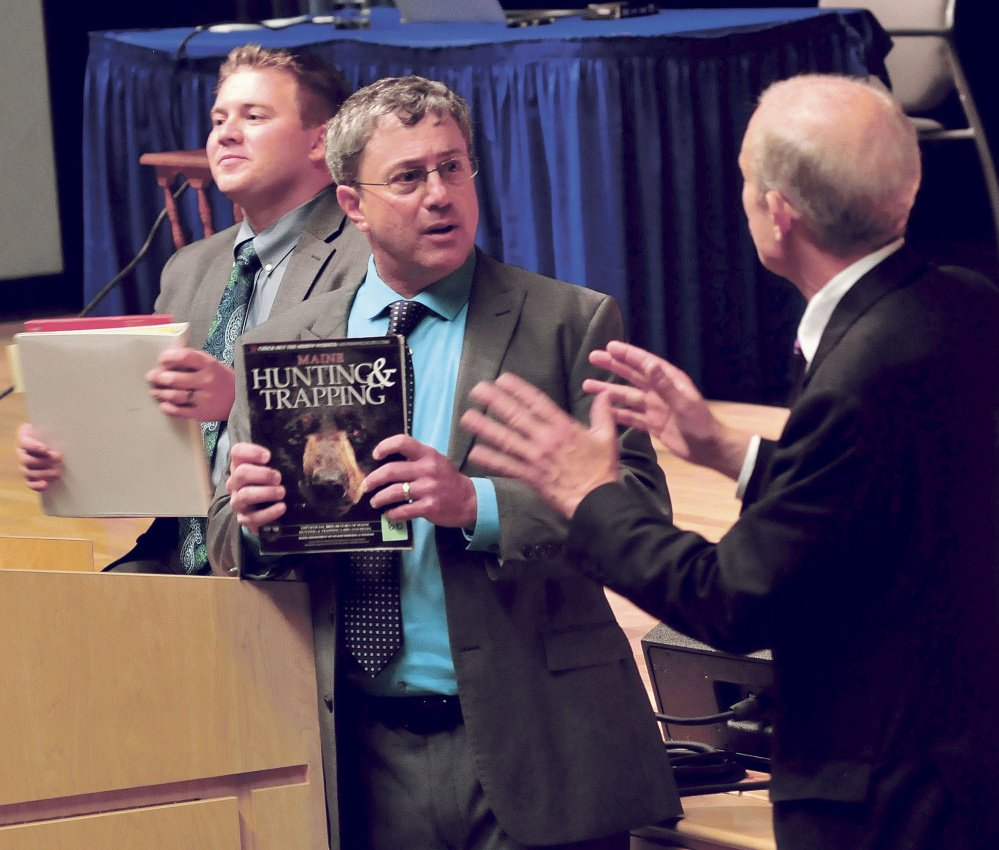 Attorney Lawrence Bloom, center, holds a hunting regulation book after arguing his client is innocent of a hunting violation following an appeal hearing with the Maine Supreme Judicial Court at Mt. Blue High School in Farmington on Wednesday. Attorneys Francis Griffin, left, and Paul Mills listen.