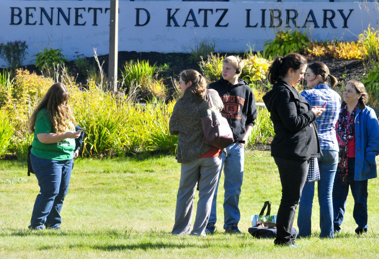 People wait outside the Katz Library at the University of Maine at Augusta Thursday afternoon.