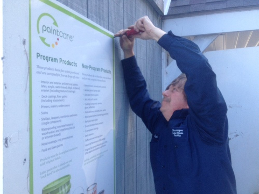 Skowhegan town employee Clyde Merrill puts up signs Thursday at the town's transfer station announcing the new Paint Care recycling program.