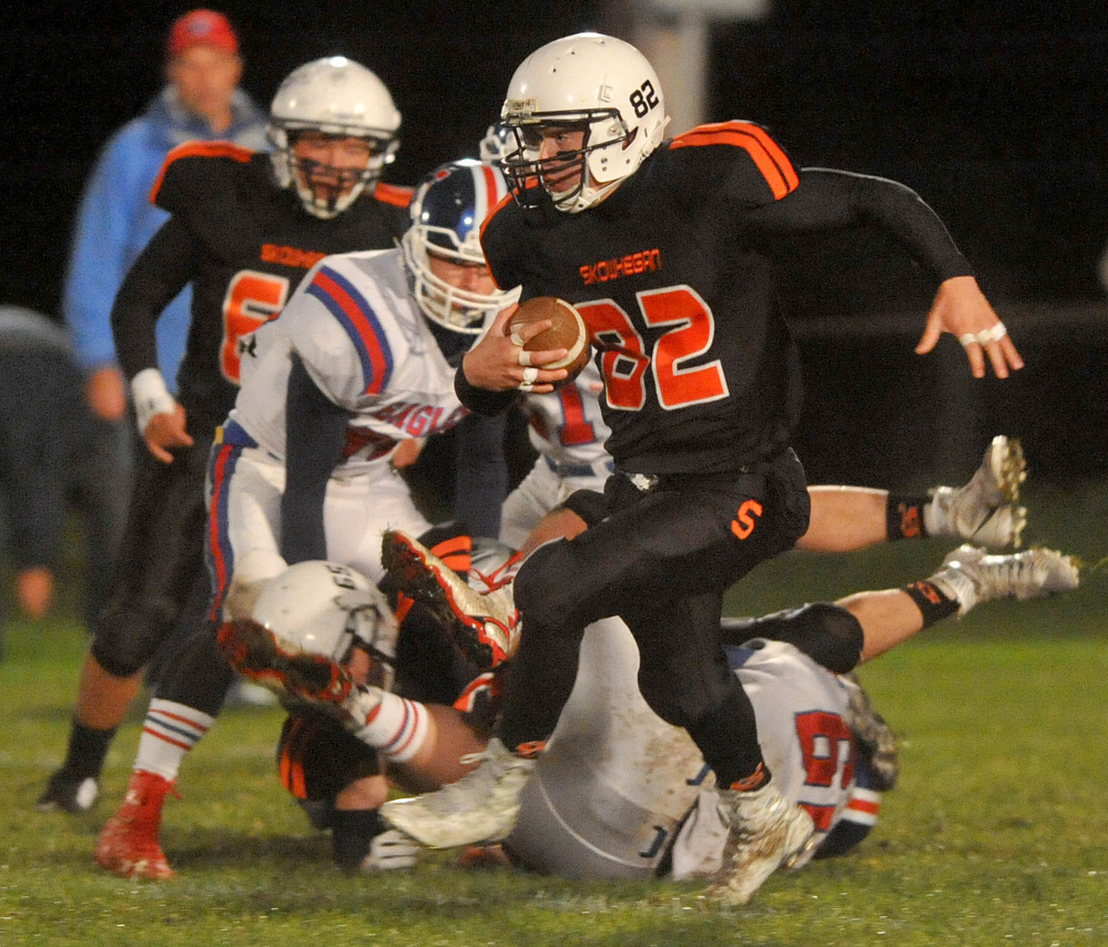 Staff photo by Michael G. Seamans   Skowhegan quarterback Garrett McSweeney (82) scrambles for extra yards as Messalonskee defenders pursue during a Pine Tree Conference Class B game Friday night at Clark Field.
