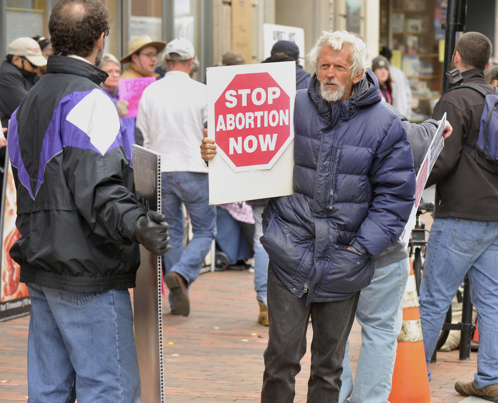 Abortion opponents line up outside the Planned Parenthood office in Portland on Saturday to call for an end to the public funding of the organization.