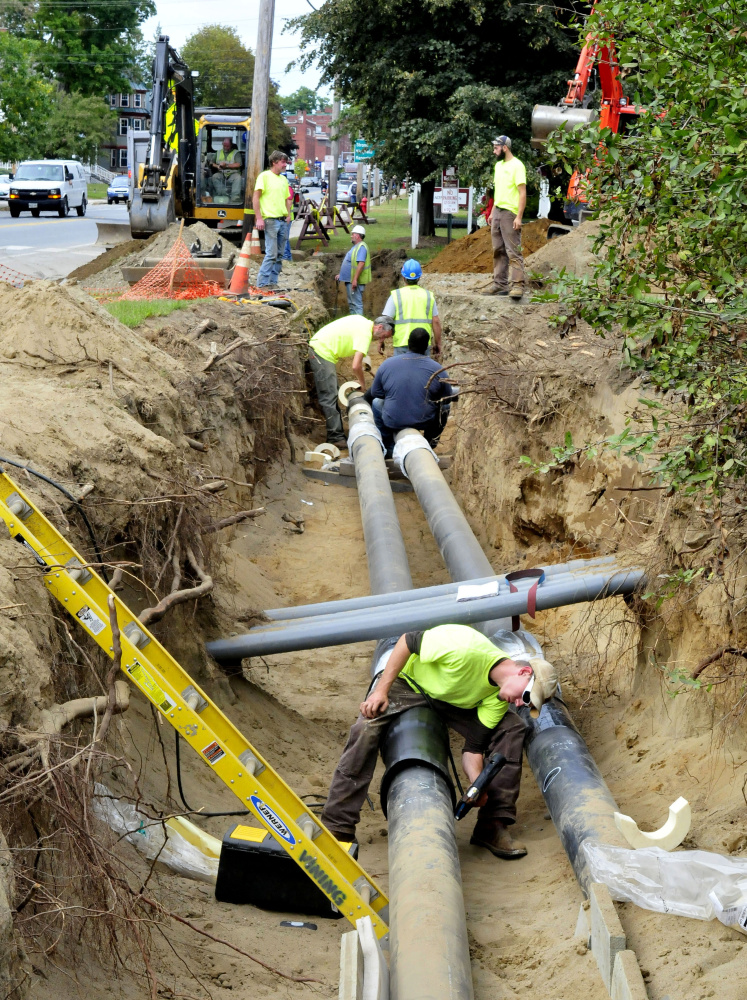 Workers lay pipes for the biomass heating system along Main Street near the University of Maine at Farmington.