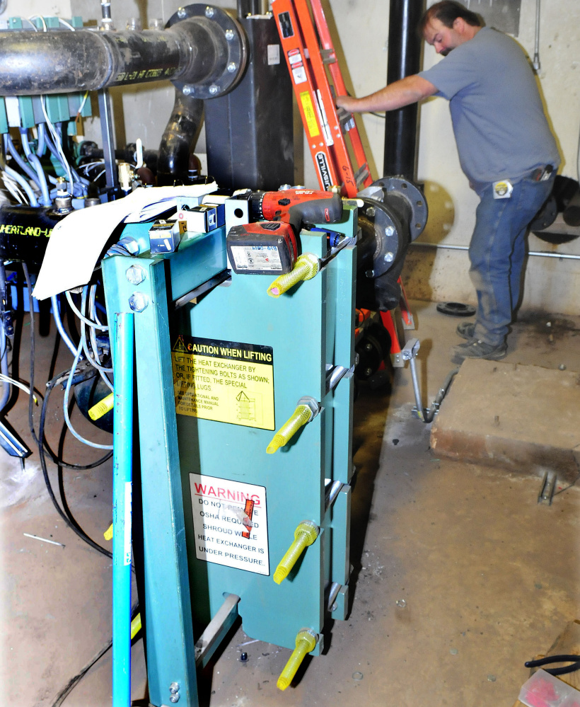 A worker installs equipment beside a compact heat exchanger for the new biomass heating system in Scott Hall dormitory at the University of Maine at Farmington. The exchanger will replace two large oil burner furnaces.