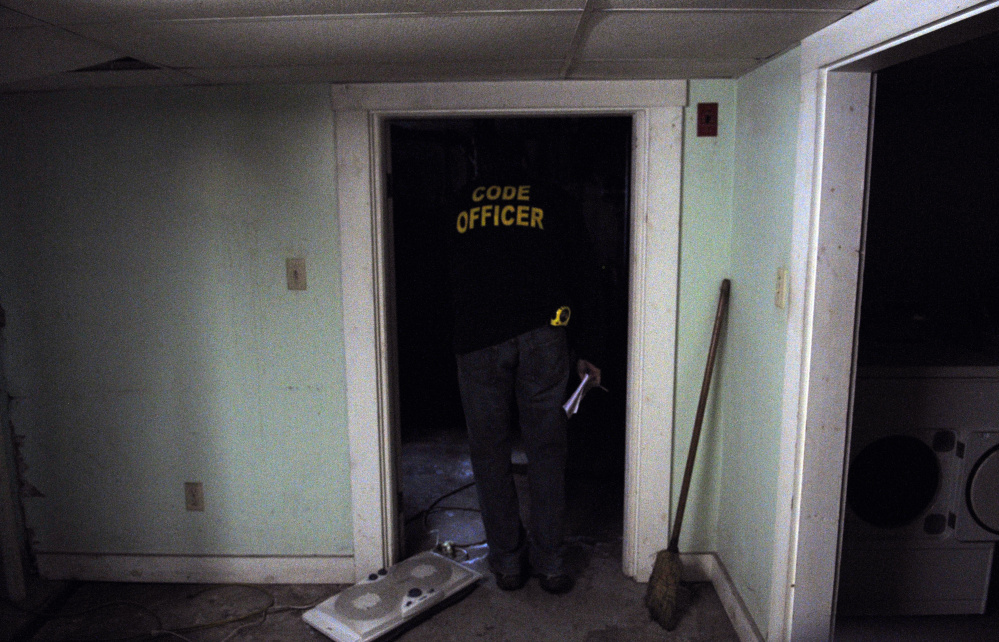 City of Augusta Code Enforcement Officer Robert Overton looks around in a basement during an inspection on Oct. 2 of an apartment building.