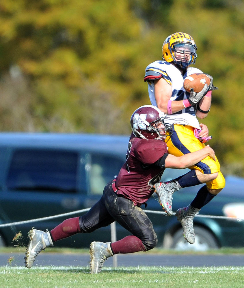 Mt. Blue High School's Christian Whitney (28) catches the ball as Nokomis High School's Cody Rice (42) defends on Saturday in Newport.