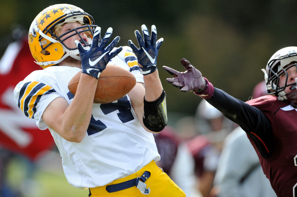 Mt. Blue High School's Nate Pratt-Holt (14) lets a ball pass through his hands for the incompletion as Nokomis High School's Colby Pinette (20) defends Saturday in Newport.