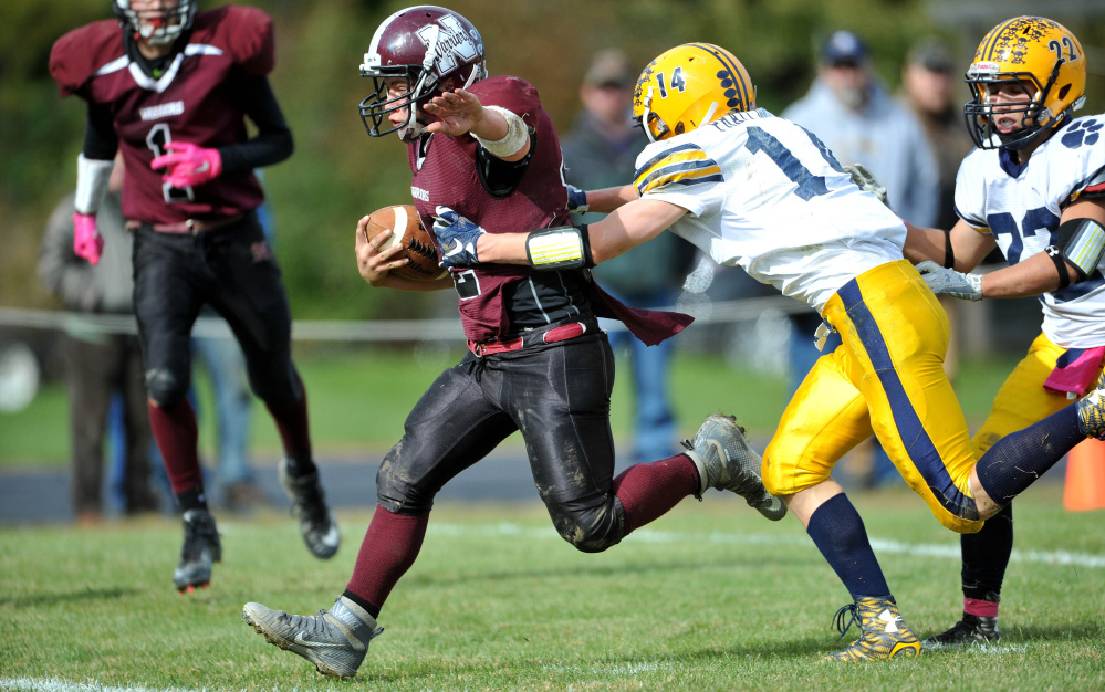 Nokomis High School's Brock Graves (12) scores a touchdown as Mt. Blue High School's Nate Pratt-Holt (14) tries to make the tackle on Saturday in Newport.