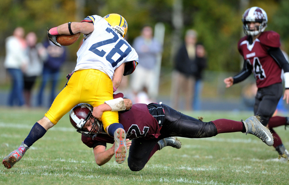 Nokomis High School's Cody Rice (42) dives to tackle Mt. Blue High School's Christian Whitney (28) on Saturday in Newport.