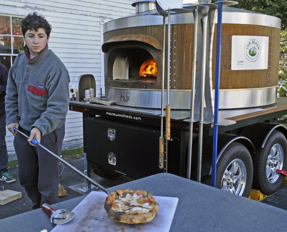 Ellis Wells pulls pizza from the wood-fired oven at 168 Main St. during harvest festivities on Saturday in Belgrade Lakes village. His uncle Sam Wells is planning to start a business selling pizzas there next summer and was offering samples during the festival.