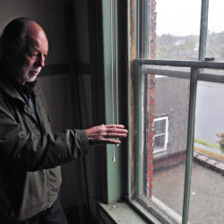 Richard Parkhurst looks at the view of the Kennebec River from a window at 287 Water St. in Augusta on Friday.